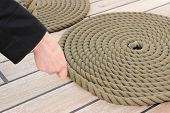 stock photo of roping  - Old nautical thick rope wrapped in spiral lying on weathered deck of yacht circle of thick rope with hand of woman - JPG