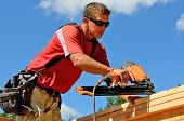 foto of top-gun  - Building contractor worker with a air nail gun nailer working on the corner of the top plate of the first floor walls on a new home construciton project - JPG