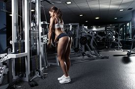foto of bum  - Nice sexy woman doing triceps workout in gym - JPG
