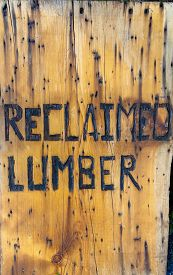 """stock photo of lumber  - """"reclaimed lumber"""" burned into board promoting reuse and recycling of old lumber - JPG"""