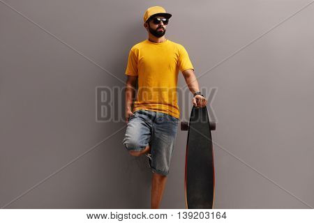 Male skater with a yellow cap holding a longboard and leaning against a gray wall