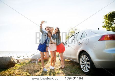 summer vacation, holidays, travel, road trip and people concept - happy teenage girls or young women
