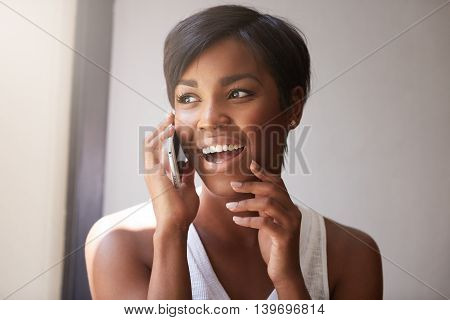 Young Attractive African Woman With Short Haircut Talking On Cell Phone To Her Friend, Looking Cheer