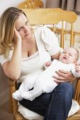 picture of mother baby nature  - Worried Mother Holding Baby In Nursery - JPG