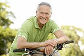 image of senior men  - Portrait of man riding cycle in countryside - JPG