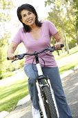Senior Woman Riding Bike In Park