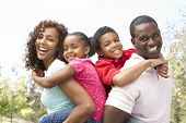 stock photo of family fun  - A portrait of happy family in park - JPG