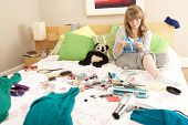 stock photo of untidiness  - Teenage Girl In Untidy Bedroom Waxing Legs - JPG