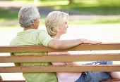 Senior Couple Sitting Together On Park Bench