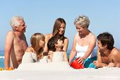 Three Generation Family Building Sandcastles On Beach Holiday