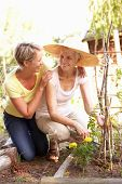 stock photo of beautiful senior woman  - Senior Woman And Adult Daughter Relaxing In Garden - JPG