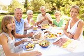 pic of extended family  - Extended Family Enjoying Meal In Garden - JPG