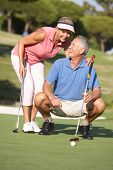 Senior Couple Golfing On Golf Course Lining Up Putt On Green