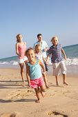 pic of summer fun  - Portrait Of Running Family On Beach Holiday - JPG