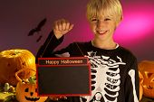 Halloween party with a boy child holding sign