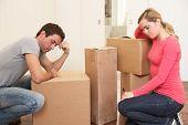 Young couple looking upset among boxes