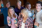stock photo of underage  - Group Of Teenage Friends Dancing And Drinking Alcohol - JPG
