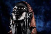 Porträt einer künstlerischen Frau mit schwarzer Farbe bemalt und spangled. Körper-Malerei-Projekt. Juwelier