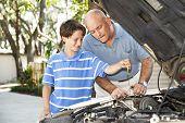Padre e hijo trabajando juntos en el coche.  El hijo está comprobando el aceite.