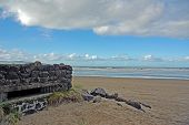 stock photo of emplacements  - Second world war pillbox on the beach at Downhill disguised as a pile of stones - JPG