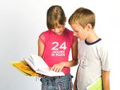 stock photo of girl reading book  - Young girl and boy reading book  - JPG