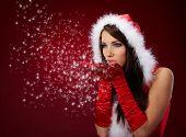 Portrait of beautiful sexy Girl wearing Santa Claus Kleidung auf rotem Hintergrund