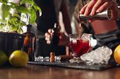 Постер, плакат: Bartender Preparing Fresh Negroni Cocktail
