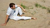 Low spirits man sitting on the sand