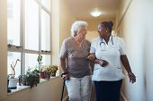 Smiling Healthcare Worker And Senior Woman Walking Together poster