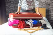 Travel And Vacation Concept, Happiness Young Woman Packing A Lot Of Her Clothes And Stuff Into Suitc poster
