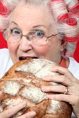 An old lady with hairroller on, biting on a loaf of bread.