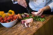 Master Chef hands putting salt on juicy slice of raw steak with vegetables around on a wooden table poster