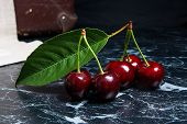 Several Red Sweet Cherries And Big Green Leaf On Dark Marble Background.. poster