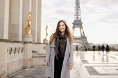 Beautiful Young Woman In Grey Coat Standing On Trocadero Square Near Gilded Statues And Eiffel Tower poster