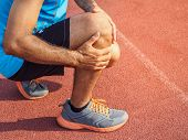 Knee Injuries. Sport Man With Strong Athletic Legs Holding Knee With His Hands In Pain After Sufferi poster