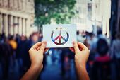 Close Up Of Woman Hands Holding A White Paper Sheet With Peace Symbol Over A Crowded City Street Bac poster