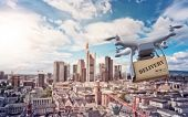 multicopter drone with package flying over the cityscape of Frankfurt am Main, Germany, financial ca poster