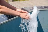 Hand Touch The Fountain. A Stream Of Water From The Fountain Is Touched By Hand. poster