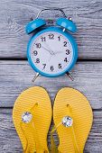 Yellow Flip Flops And Blue Alarm Clock. Luxury Sandals With Brilliants. Dark Wooden Surface Backgrou poster