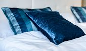 Blue Silky Hotel Room Bedding Pillows And Sheets On Bed. poster
