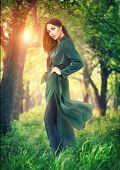 Beauty fashion model girl posing over blooming trees, enjoying nature in spring apple orchard. Beaut poster