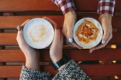 Female Hands Holding Cups Of Coffee On Wooden Table Background. Big Mugs Of Hot Latte Drink Warming  poster