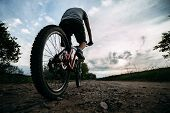 Young Man In Helmet Riding A Bicycle Along Country Road On Sunset Sky Background. Bicycle Sports, Tr poster