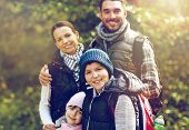 travel, tourism, hike and people concept - happy family walking with backpacks in woods poster