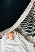 The Newborn Baby Sleeps Sweetly And Calmly In A Woven Light Hammock On A Dark Background. poster