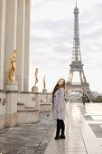 European Woman In Grey Coat Standing On Trocadero Square Near Gilded Statues And Eiffel Tower In Par poster