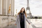 Cheerful Female Peson In Grey Coat Standing On Trocadero Square Near Gilded Statues And Eiffel Tower poster