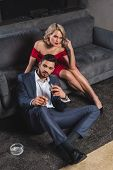 Handsome Man In Suit Holding Cigar And Glass Of Whisky While Spending Time With Seductive Woman In R poster