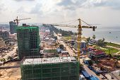Construction High-rise Building By Crane In City Near Sea. Construction Of Expensive Hotels In Resor poster