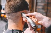 Barber Shaves The Clients Head With A Electric Trimmer. Young Bearded Man Getting Haircut By Hairdre poster